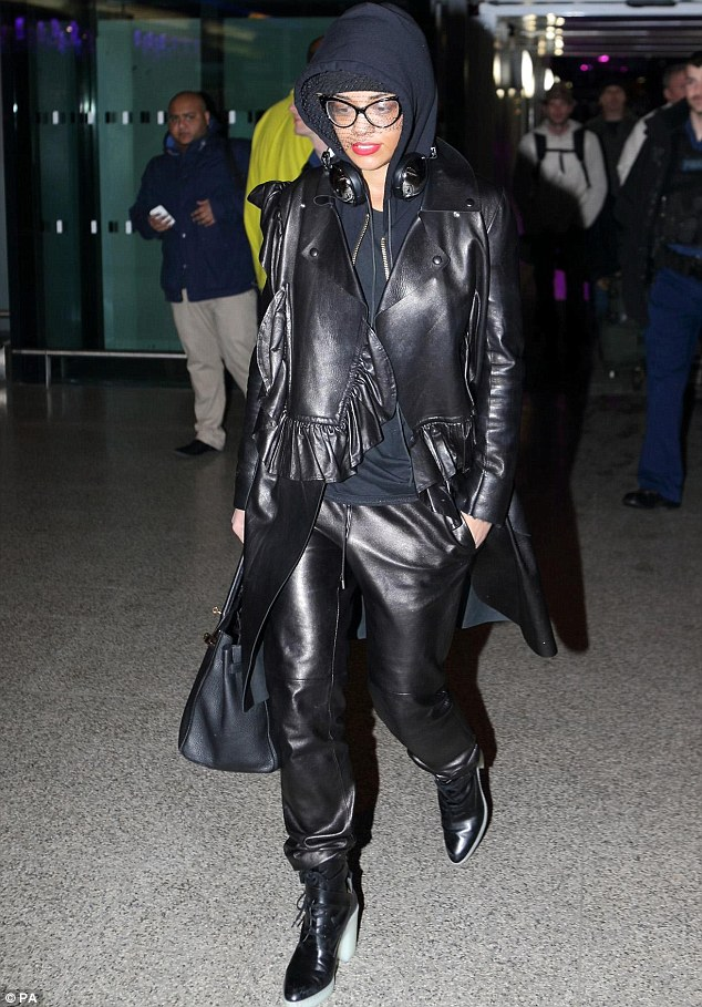 Taking the leather look to a whole new level: Rita Ora opts for a leather jacket, leather trousers, leather shoes and a veil for her flight