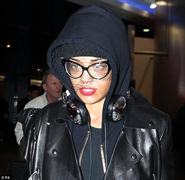 Don't worry Rita, you'll be there soon! Rita Ora looks grumpy as she prepares to leave the UK - she tweeted she was bored out of her mind on the plane
