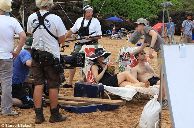 As you do: Peter and Monica stretch out on the beach as they're surrounded by cameras during filming