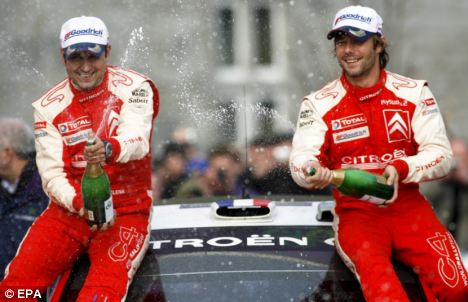 Drenched: Loeb celebrates one of his nine Rally World Championship victories but he will not defend his title this year