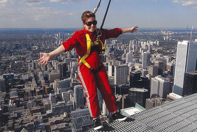 A brave Amy dangles off the CN Tower 1,200ft above Toronto