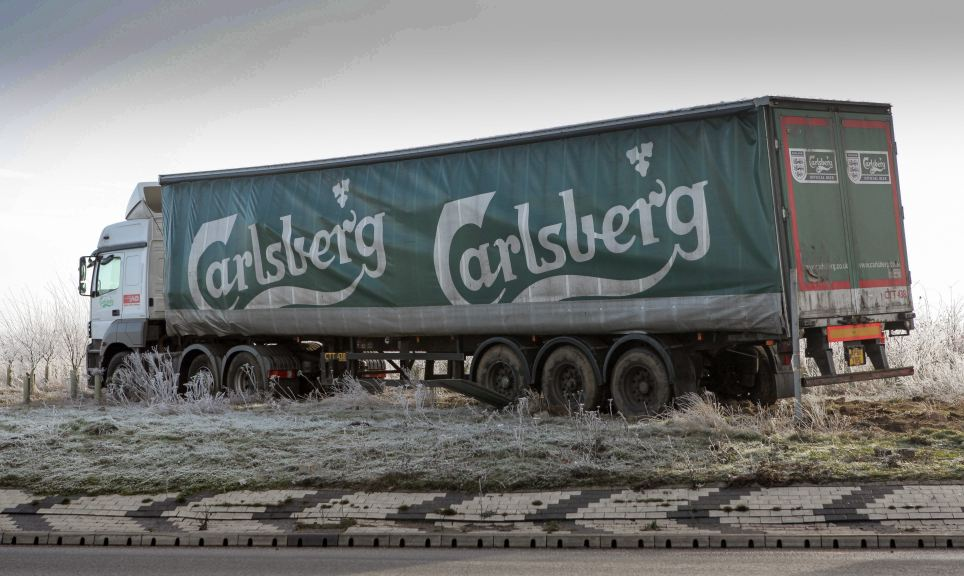 Beer battered: A 44-ton Carlsberg truck got stuck in the middle of the Black Cat roundabout in Roxton, Beds, at round 4am yesterday morning and couldn't be recovered until midday