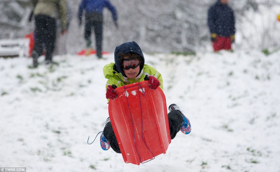 Playtime! Luca Pegram, 12, sledges off a snow jump in Brandon Hill park in Bristol city centre with more than 2,000 schools shut