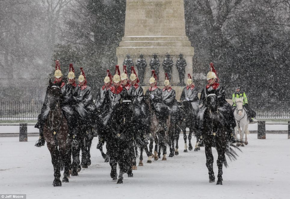 Royal duty: Tourists have not been left disappointed in London, where the changing of the Guard has taken place as usual in Horse Guards Parade