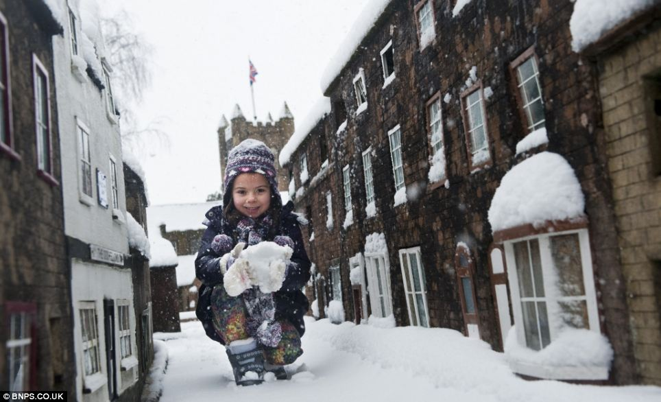Gleeful: More than 2,000 schools closed today with Wimborne Model Town in Dorset becoming six-year-old Maya Wheeler's personal winter wonderland