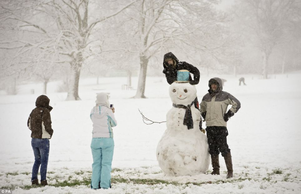 Frosty fun: Families take photographs of their impressive snowman in Victoria Park, Totterdown, Bristol as they enjoy a day of leisure