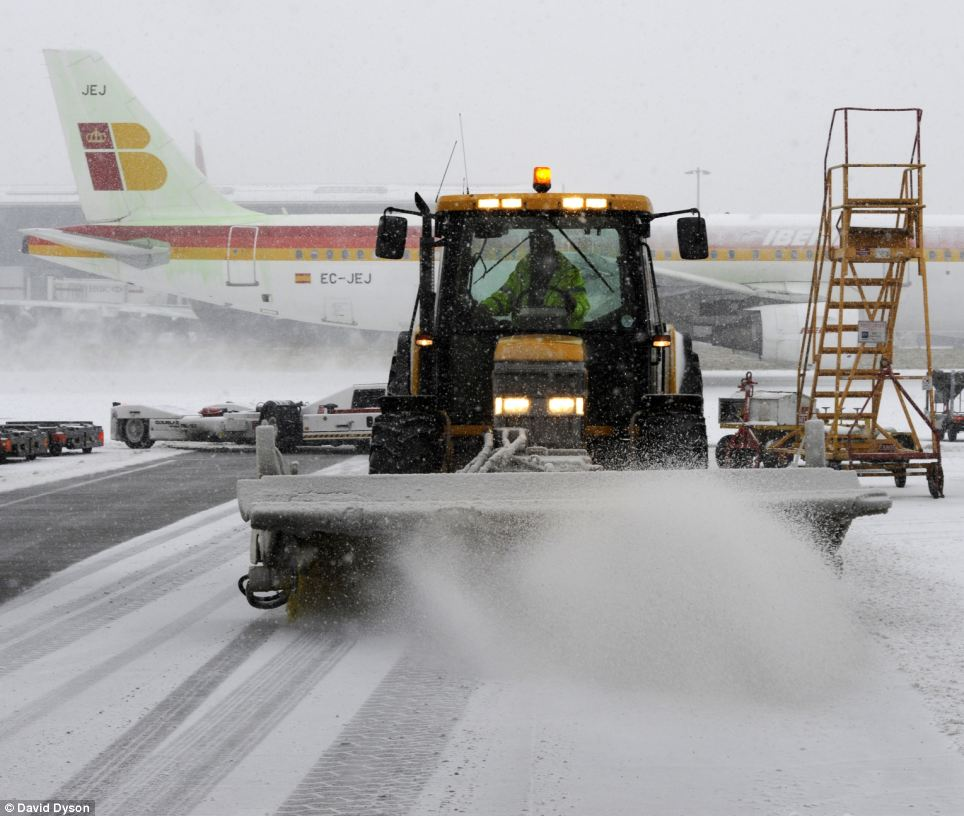 On the runway: Tractors clear snow from the stands at Heathrow, where there were 404 cancellations