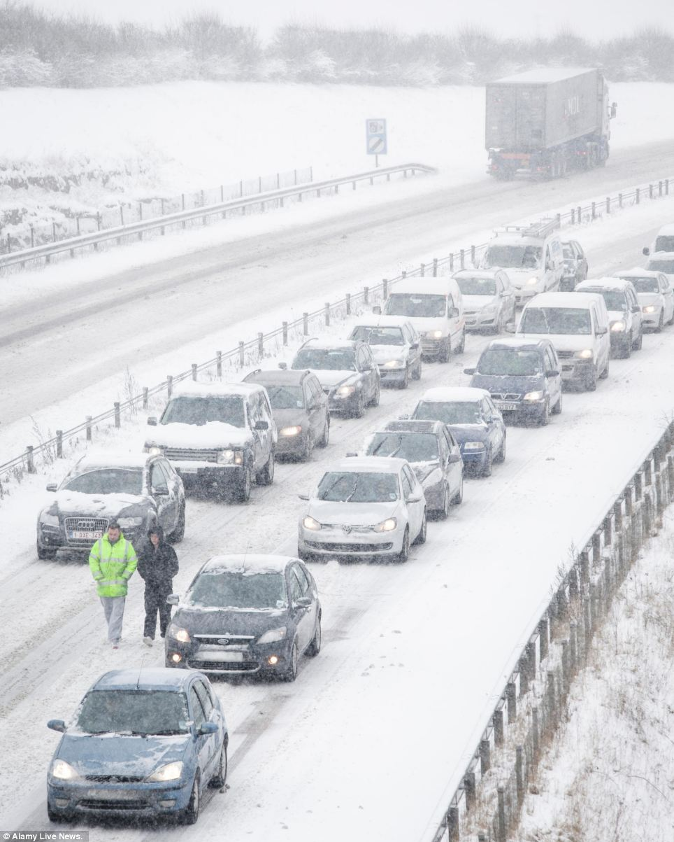 Motorists wander on the road as traffic grinds to a halt on the A417 outside Cirencester, between Swindon and Birdlip Hill, Gloucestershire