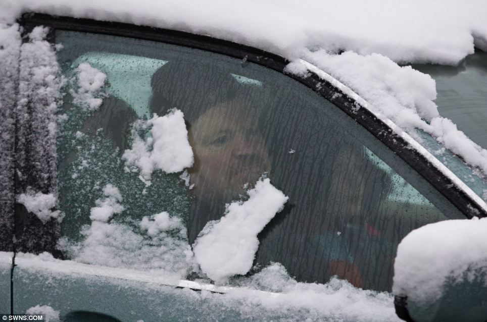 Hampered: A motorist is determined to drive his children in his snow covered car  despite the icy conditions in Plymouth