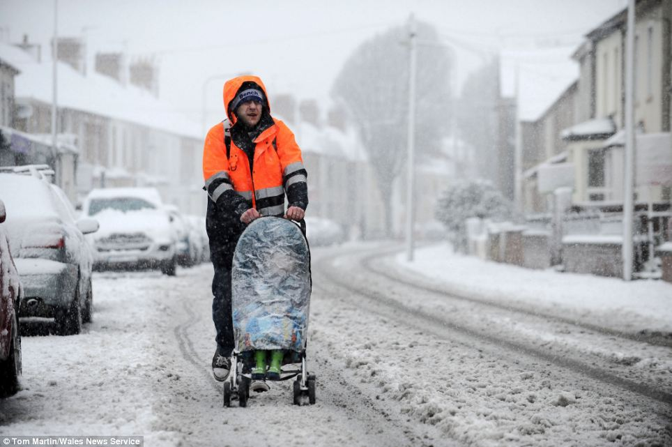 Brave face: A father pushed his youngster through the snow in Cardiff this morning, with the empty road proving an easier route than the icy pavement