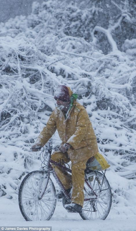 Tyre-ing: A cyclists peddles away regardless of the tough conditions facing home in Swansea