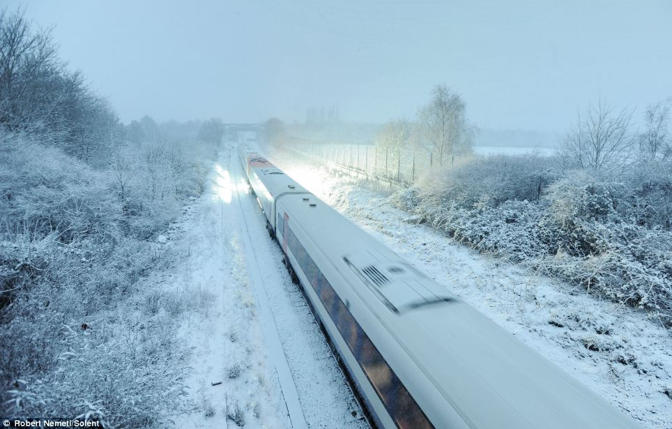 Full steam ahead: A South West Train continues in Bournemouth, where the snow on either side of the tracks is lit up by the spark from the electric connections