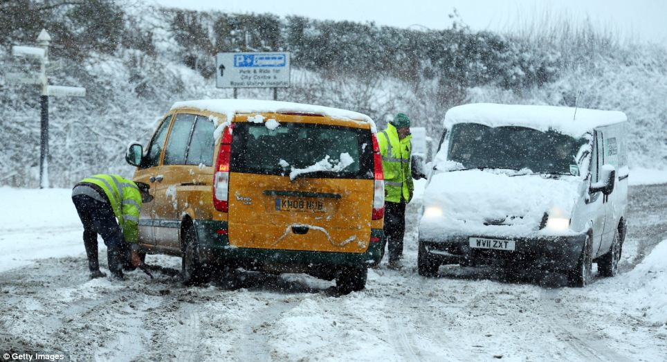 Helping hand: Motorists help each other out on the normally busy A367 after a van slipped in the snow