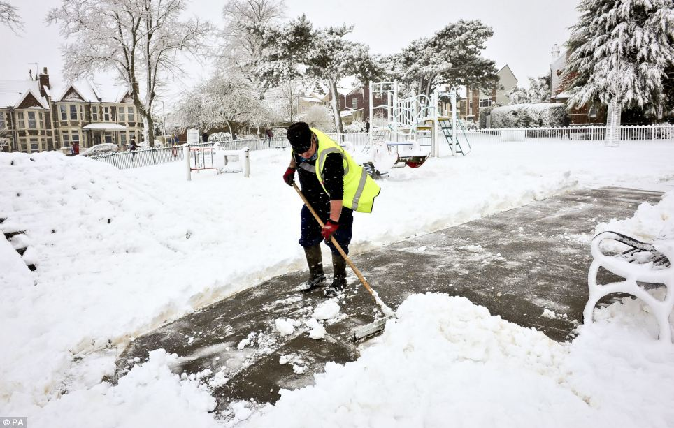 Playtime: A man clears a path inside the children's play area at Victoria Park in Bristol, which was expected to be busy with families enjoying the snow