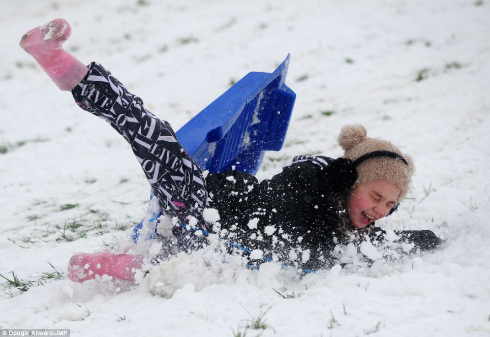Ouch: A young girl takes a tumble while taking full advantage of a day off school by sledging in Perrett's Park, Bristol