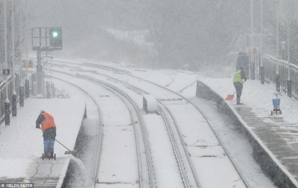 Team effort: Workers put their back into clearing the snow from platforms at Petersfield Station, Hampshire, as people rally together to overcome the conditions