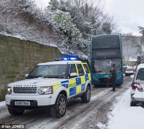 Public service: Police officers lend a helping hand to a bus driver in Alnwick in Northumberland, after his vehicle got into trouble on an icy stretch of road
