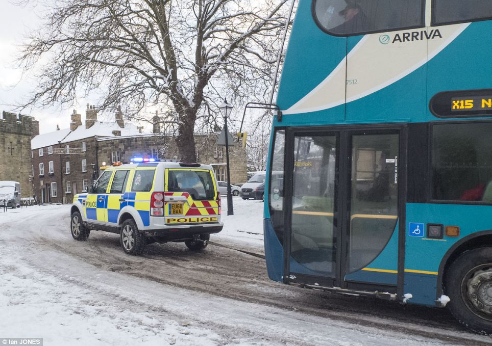 Pulling together: A police Discovery vehicle tows a bus up a hill as officers do their bit to keep things moving in Alnwick in Northumberland