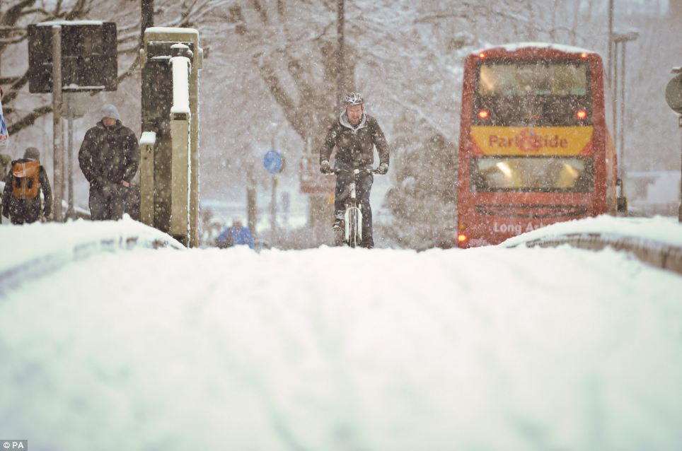 All aboard: A bus attempts to complete its route in Bristol, while others opt to either walk or cycle to work instead