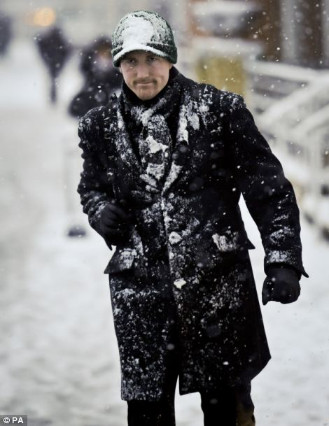 Snow man: This worker was slowly covered in snow as he trudge to work in Bristol city centre, which was transformed into a sea of white