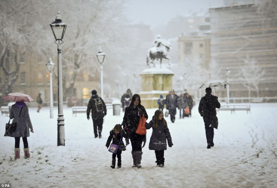 Life goes on: People in Queens Square, Bristol, attempt to go about their day as usual despite the severe weather