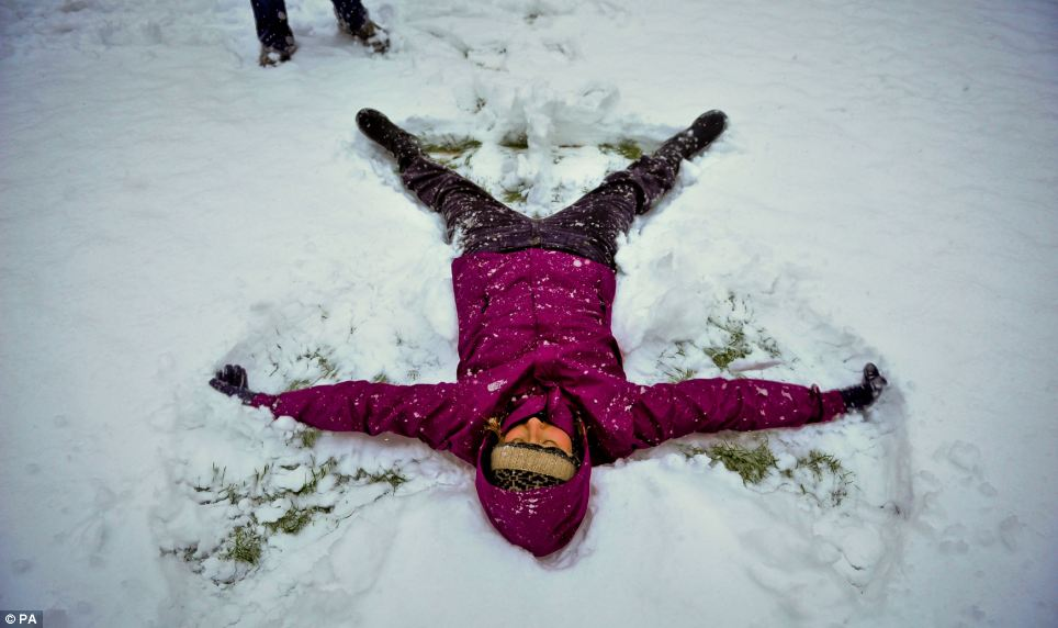 Snow much fun: A young girl makes snow angel on the ground in Bristol, where many youngster are enjoying a day off school