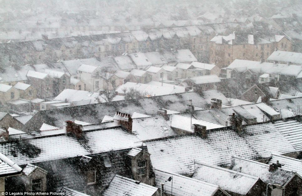 From on high: Rooftops are covered in snow in the Mount Pleasant area of Swansea in south Wales, where snow fell overnight and into the morning