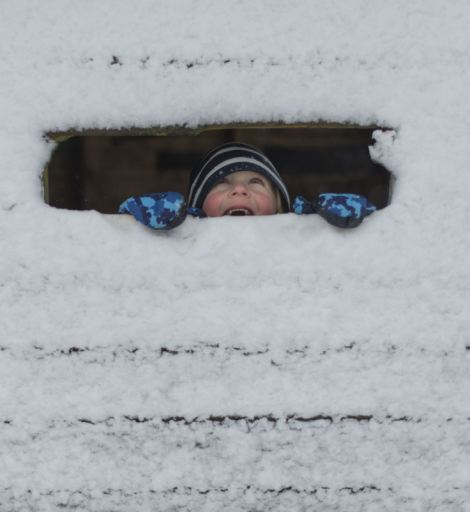 Vantage point: A young boy finds some shelter but still gets to look out at his snowy surroundings in High Bickington, Devon