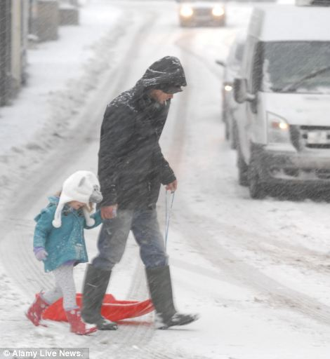 Walk home: A man and young girl make their way home after a day's sleding in Kington, Herefordshire