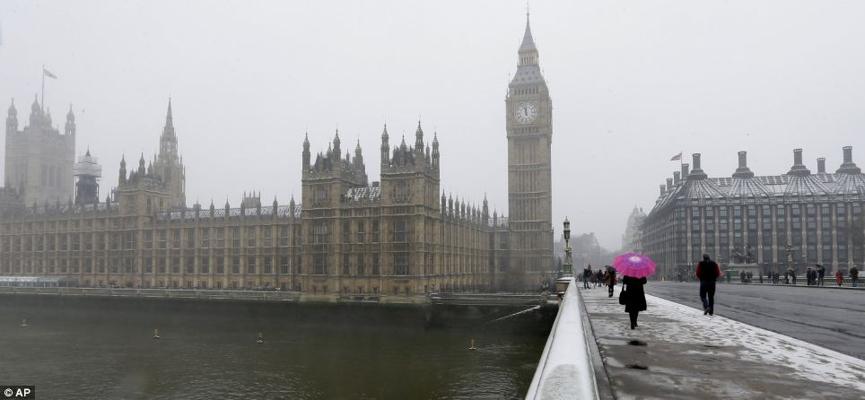 Order: Westminster Bridge in London provides a misty view of the Houses of Parliament as snows continues to fall from the skies above the capital