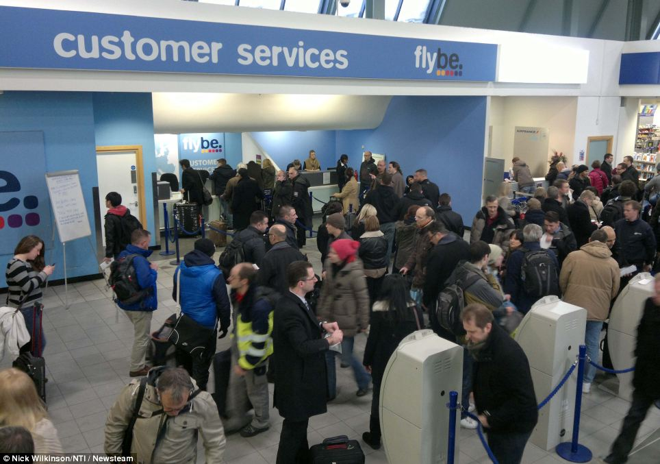 Patiently waiting: Passengers queuing at the Flybe customer service desk at Birmingham Airport, which was forced to close because of the weather