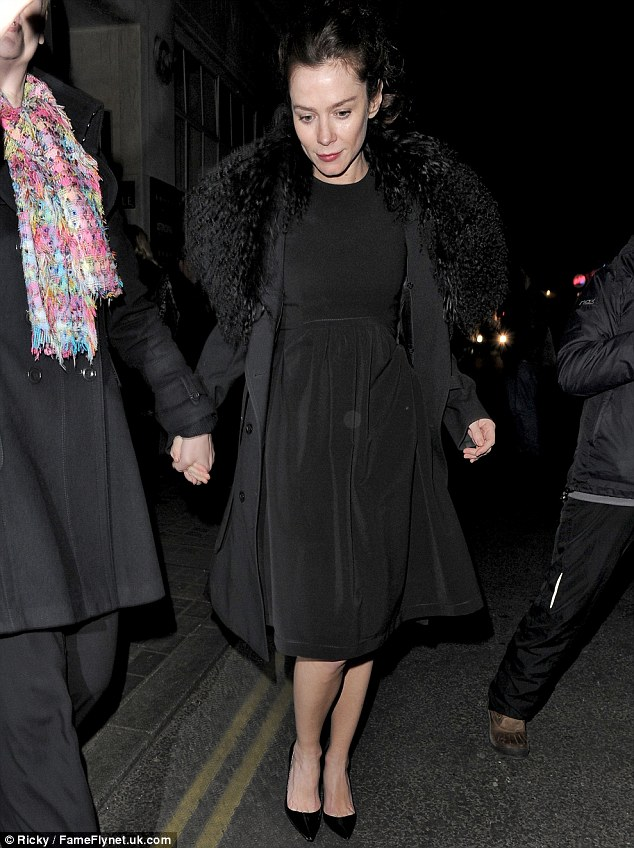Elegant: The star opted for a more classic ensemble as she left the theatre on Thursday night, teaming a simple black dress with stilettos and a faux fur-lined coat