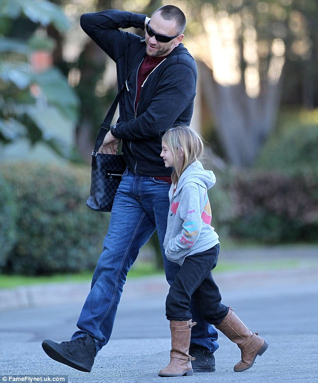 Doting: Martin was seen taking care of Heidi's daughter Leni on Tuesday while the supermodel was at work