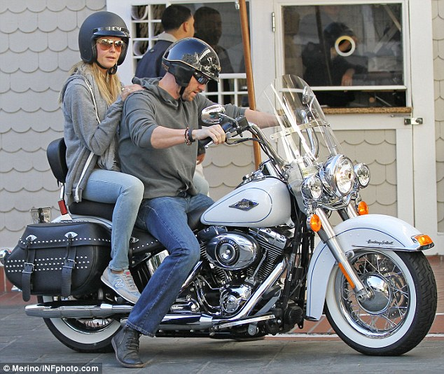 All aboard: With a pair of Aviator shades shielding her eyes, Heidi popped on a heavy black helmet as she mounted the passenger seat and wrapped her arms around a protective Martin