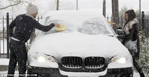 Bonding experience: The couple didn't have any gloves on as they painstakingly scrubbed the snow off the car