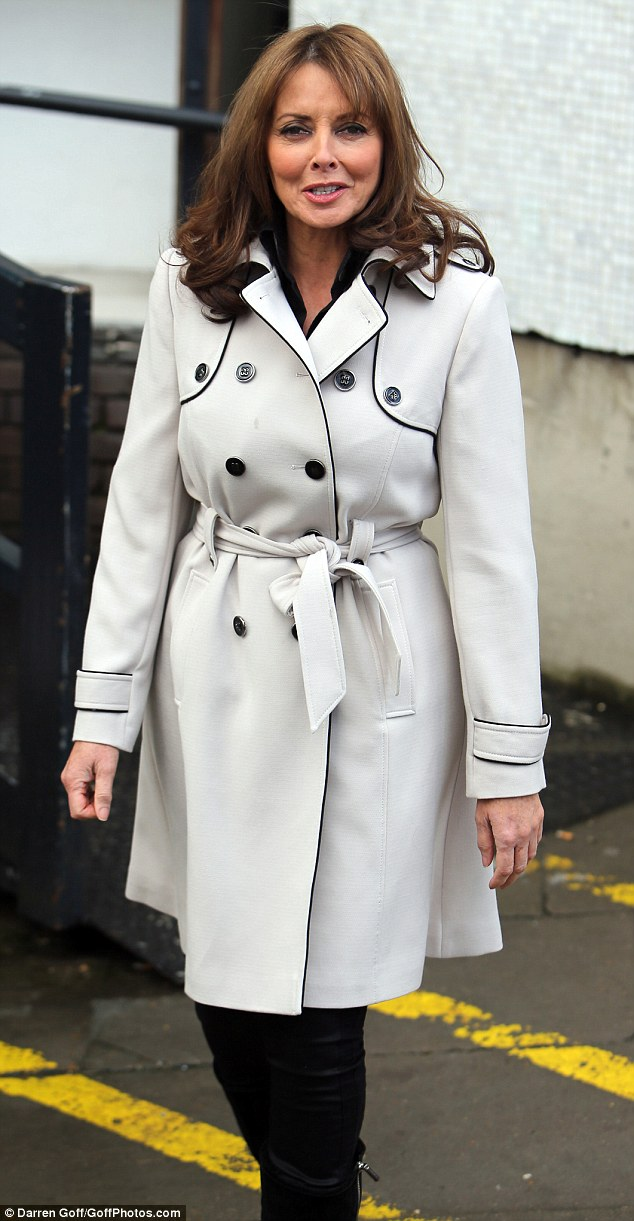 Back in the mac: Carol Vorderman looks ultra chic in her white coat with piping which complimented her new dark 'do