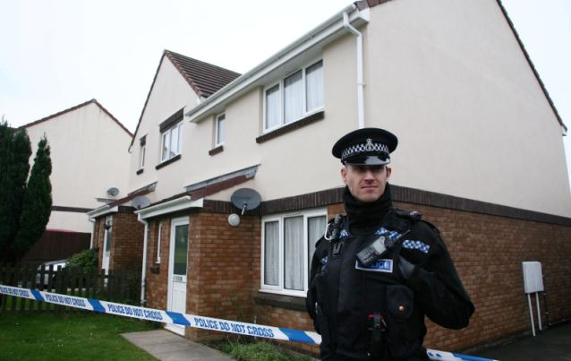 Crime scene: A police officer stands outside the home in Modbury, Devon, following the death of Shaun O'Neil