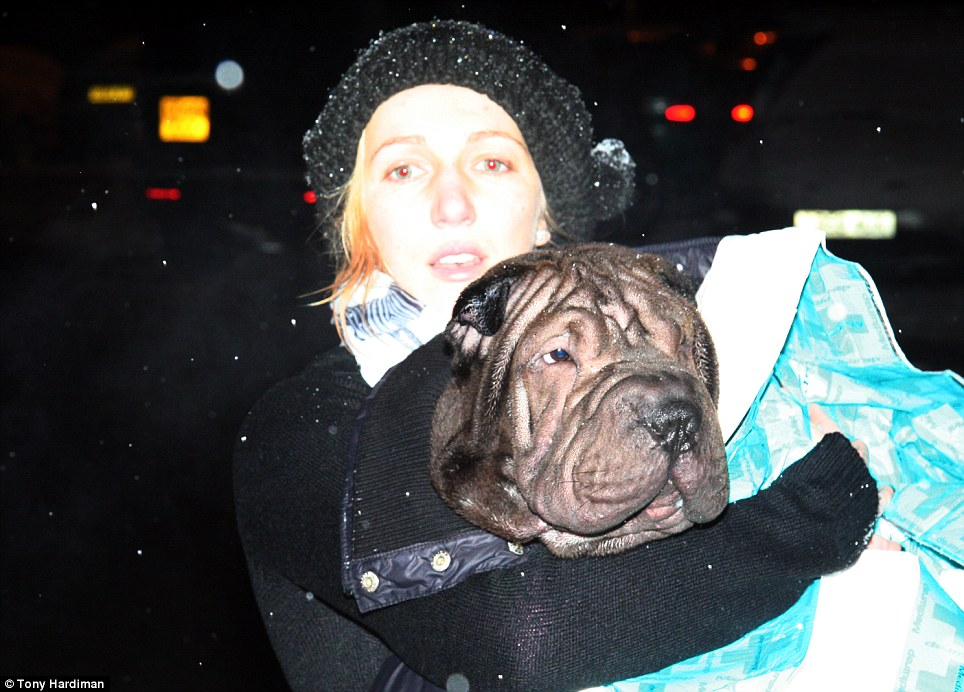 Relief: This woman looks drained clutching the dog that was lucky to survive after it fell into an icy lake late yesterday