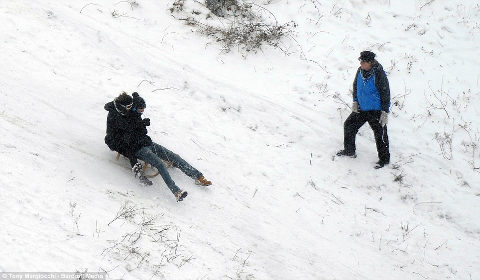 Hairy: A couple head down a huge hill watched by another sledger on Dunstable Downs in Bedfordshire