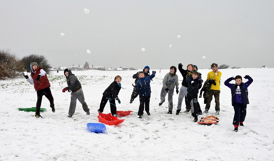 Great fun: Children in Blackpool play in the snow as schools are closed in the town and across much of the country