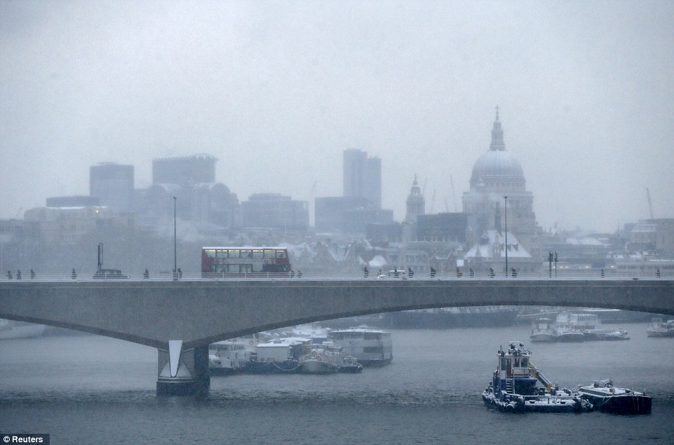Trudge: Commuters walk over Waterloo Bridge in the snow in central London today but many were not able to get into work because of problems on the railways and roads