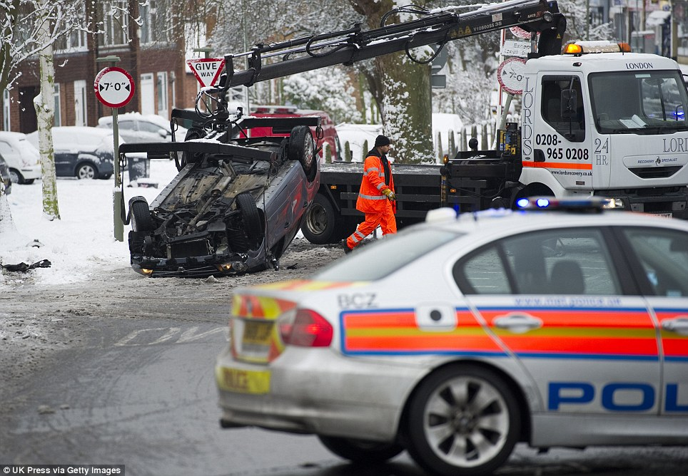 Flipped: A taxi misjudges a width restriction and crashes his car due to poor road conditions in Barnet north London as motorists struggle to cope