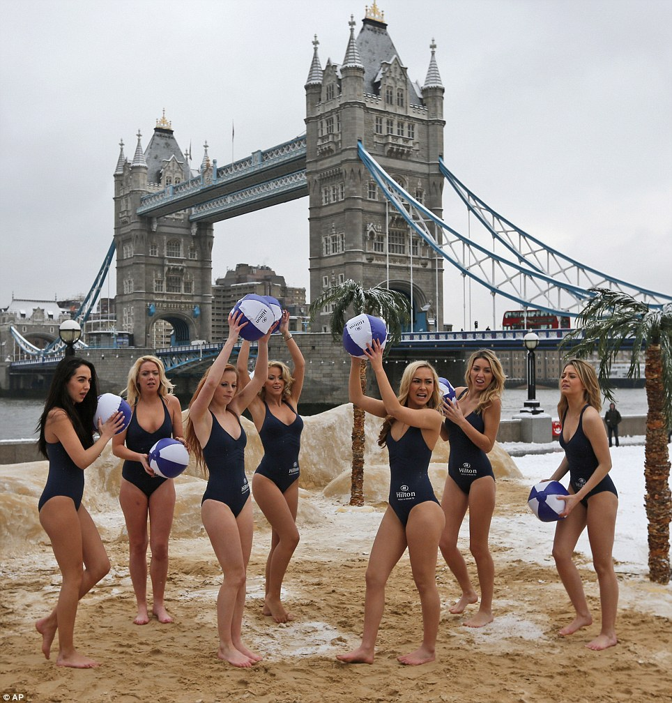 Bold: These models wearing just swimsuits pose on a pop-up beach across from Tower Bridge in central London in freezing conditions