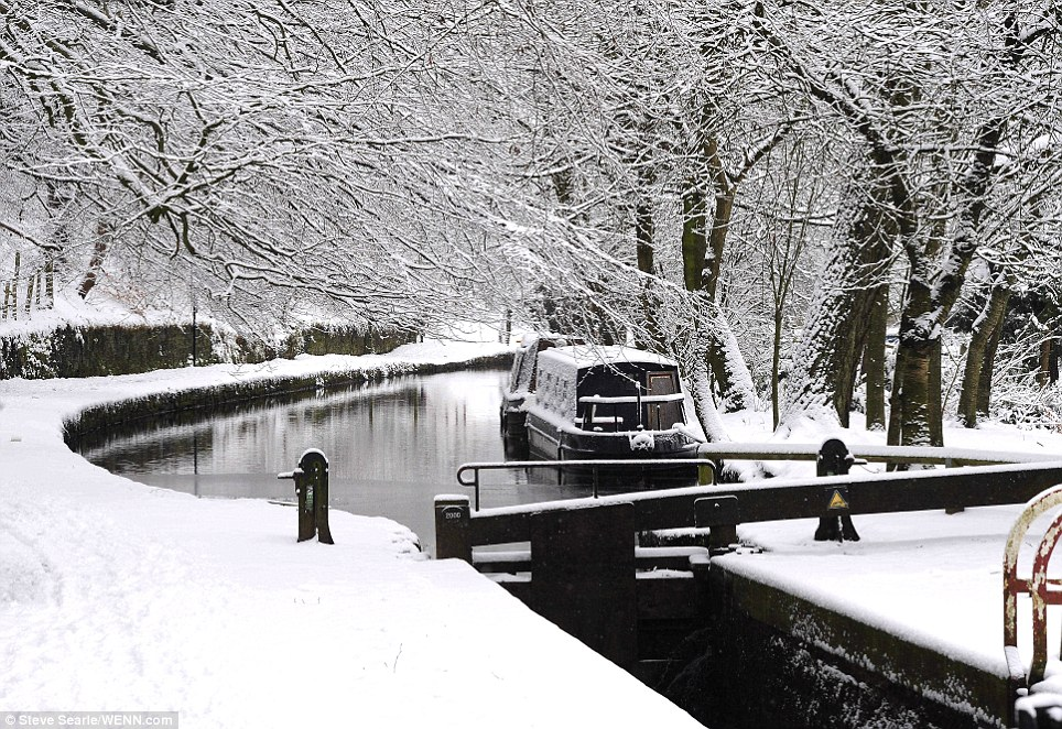Untouched: One of the north-west's many great canals, in Mossley, Greater Manchester makes a pretty picture with two boats covered in snow