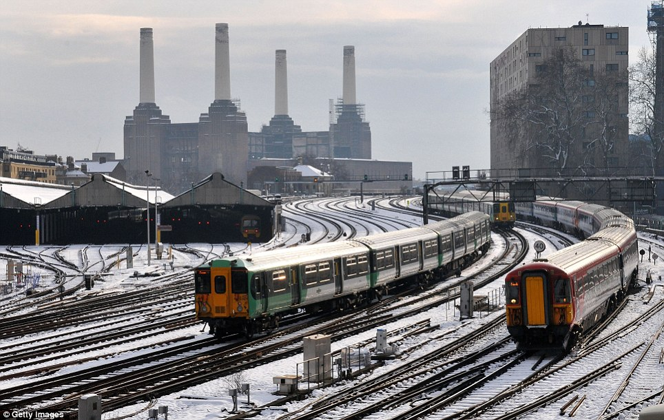 Connections: Trains travel in and out of Victoria station in front of Battersea Power Station in south-west London after the country suffered a weekend of heavy snowfall