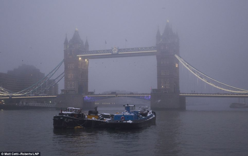 Troubled waters: London landmark Tower Bridge is shrouded in fog yesterday morning as Britain continues to struggle in cold and snowy weather
