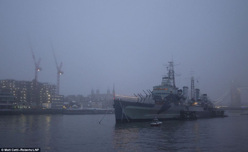 Is there light at the end of the tunnel? HMS Belfast looms out of the darkness yesterday morning after the city woke up to another day of transport chaos and school closures