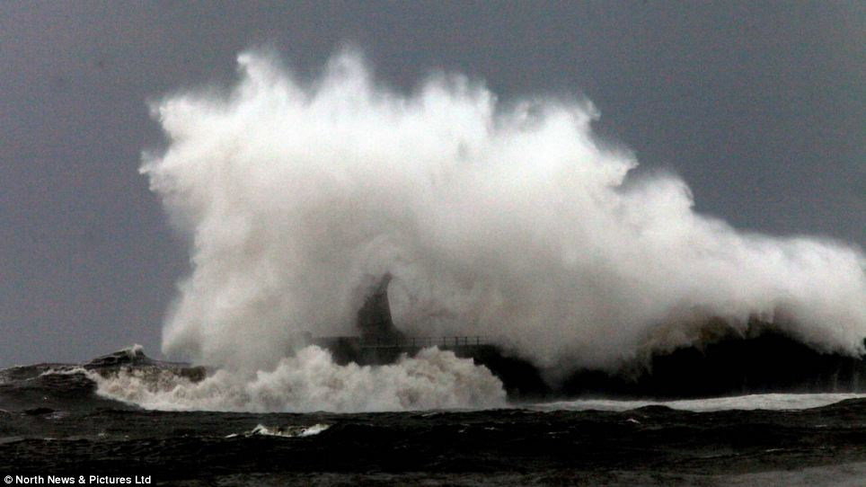 Wet 'n' wild: The pier was overwhelmed by a stormy sea at the mouth of the river - with forecasters fearing flooding as the weather gets milder this weekend