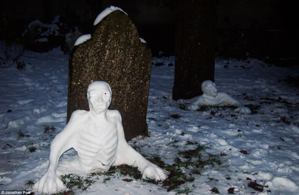 Dead cold: A spooky zombie snowmen created by Jen Hutchinson crawls out of the ground in a disused graveyard in Bristol
