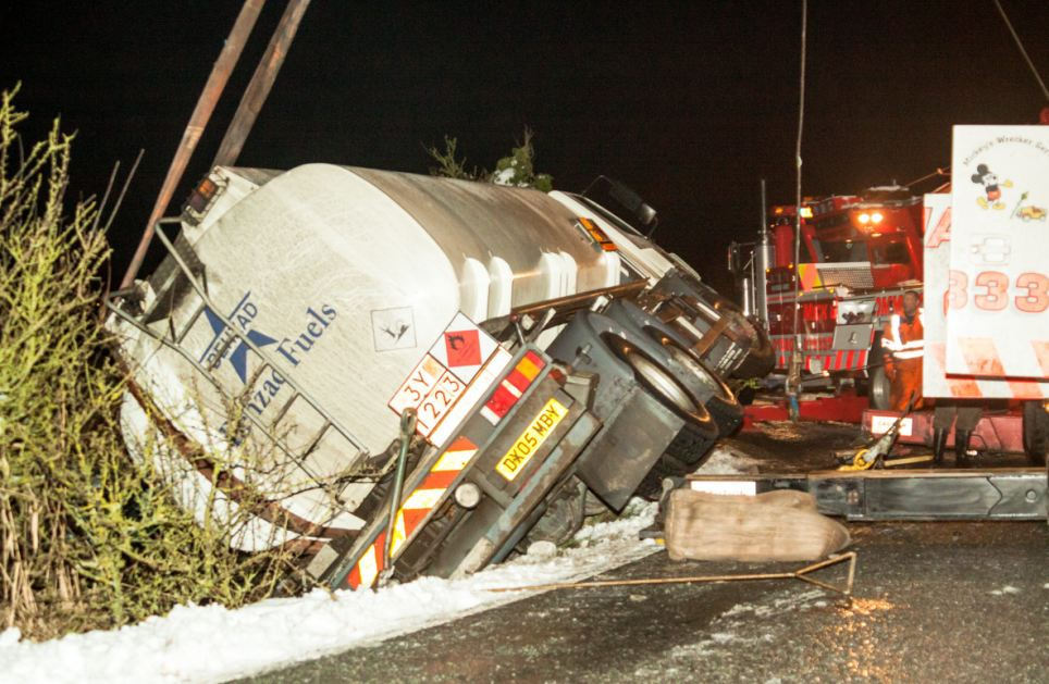 Fuelling the problem: An oil tanker carrying 13,000 litres of diesel through Sandwich, Kent, sparked a pollution alert when it slipped off a snow-covered lane on to its side in a ditch